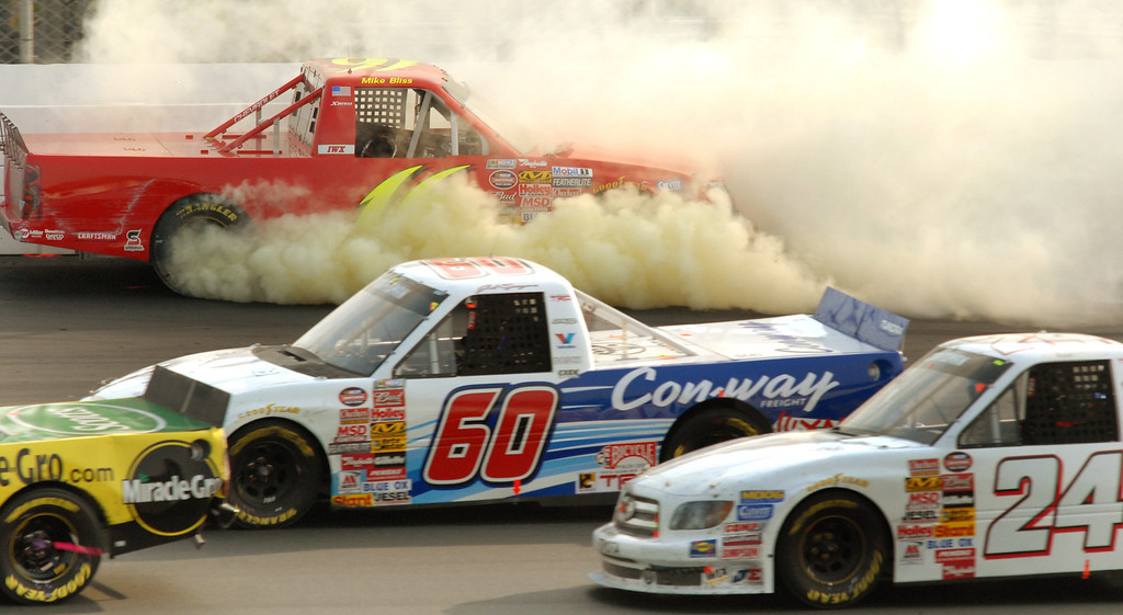 . Mike Bliss (16) crashes against the wall between turns one and two as Jack Sprague (60) and AJ Allmendinger (24) pass underneath during the NASCAR Craftsman Truck Series\' New Hampshire 200 auto race Saturday, Sept. 16, 2006, in Loudon, N.H. (AP Photo/Sandy Macys)