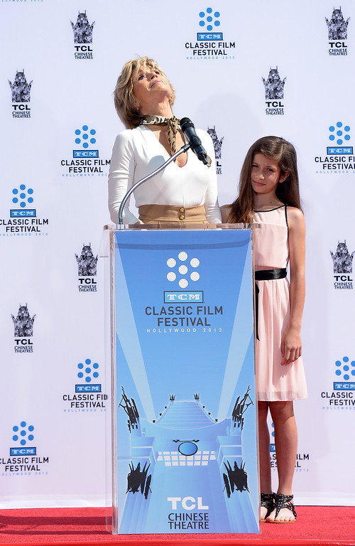. Granddaughter Viva Vadim listens as Jane Fonda looks up, speaking about her father, Henry Fonda, during Jane Fonda\'s Handprint/Footprint Ceremony during the 2013 TCM Classic Film Festival at TCL Chinese Theatre on April 27, 2013 in Los Angeles. Fonda is an American actress, writer, political activist, former fashion model, and fitness guru. She rose to fame in the 1960s with films such as Barbarella and Cat Ballou. She has won two Academy Awards, an Emmy Award, three Golden Globes and received several other movie awards and nominations during more than 50 years as an actress. After 15 years of retirement, she returned to film in 2005 with Monster-in-Law, followed by Georgia Rule two years later. She also produced and starred in over 20 exercise videos released between 1982 and 1995, and once again in 2010.  (JOE KLAMAR/AFP/Getty Images)