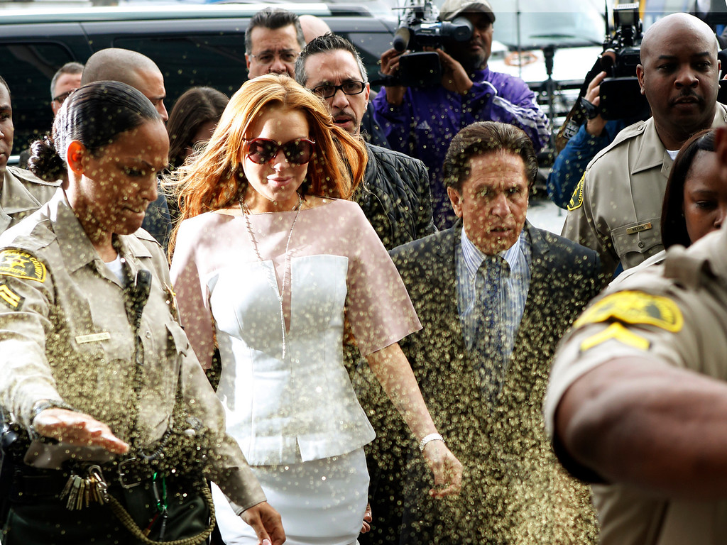 . Actress Lindsay Lohan is showered with gold glitter, second left, as she walks with her attorney Mark Heller, for her trial Monday, March 18, 2013, at  Los Angeles Superior court. Lohan is charged with three misdemeanor counts stemming from a crash on Pacific Coast Highway. She is charged with willfully resisting, obstructing or delaying an officer, providing false information to an officer and reckless driving. She is also accused of violating her probation in a misdemeanor jewelry theft case. (AP Photo/Damian Dovarganes)