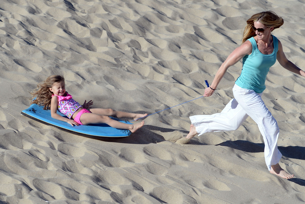 . Ali Malone gives her daughter Peyton, 4, a ride on a boogie board down a sand berm on the beach near the Hermosa Beach pier. The day after Christmas seemed more like the Fourth of July as people flocked to the beach Thursday, December 26, 2013, in Hermosa Beach, CA.  Photo by Steve McCrank/DailyBreeze