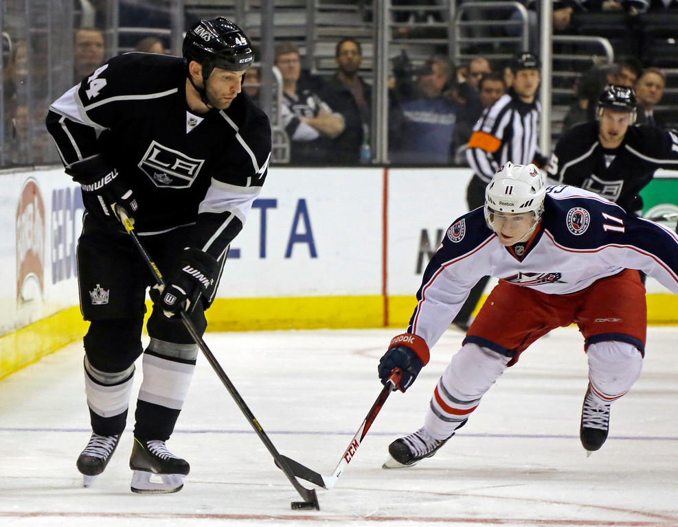. Los Angeles Kings defenseman Robyn Regehr (44) and Columbus Blue Jackets left wing Matt Calvert (11) battle for the puck in the first period of an NHL hockey game in Los Angeles, Thursday, April 18, 2013. (AP Photo/Reed Saxon)