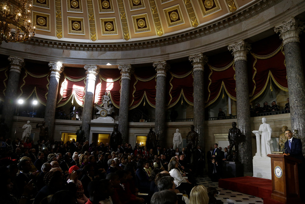 Description of . President Barack Obama speaks in the Capitol Rotunda on Capitol Hill in Washington, Wednesday, Feb. 27, 2013, during the unveiling of a statue of Rosa Parks, second from left. (AP Photo/Charles Dharapak)