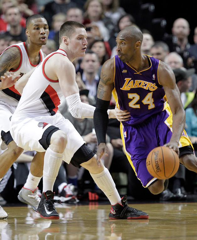 . Los Angeles Lakers guard Kobe Bryant, right, drives on Portland Trail Blazers guard Damian Lillard, left, and forward Luke Babbitt  during the second half of an NBA basketball game in Portland, Ore., Wednesday, April 10, 2013.  Bryant scored 47 points as the Lakers won 113-106.(AP Photo/Don Ryan)