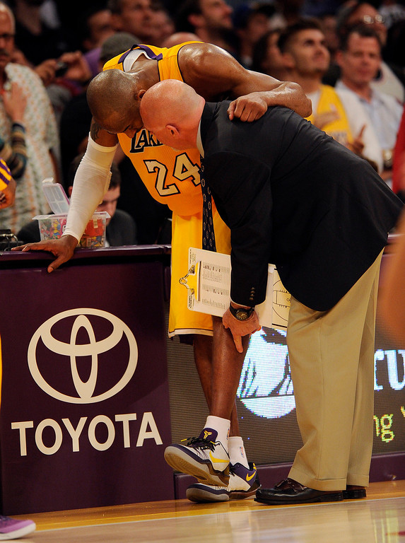 . Lakers\' Athletic trainer Gary Vitti looks Kobe Bryant #24 after he hurt his ankle during their game against the Warriors at the Staples Center in Los Angeles Friday, April 12, 2013. The Lakers beat the Warriors 118-116. (Hans Gutknecht/Staff Photographer)
