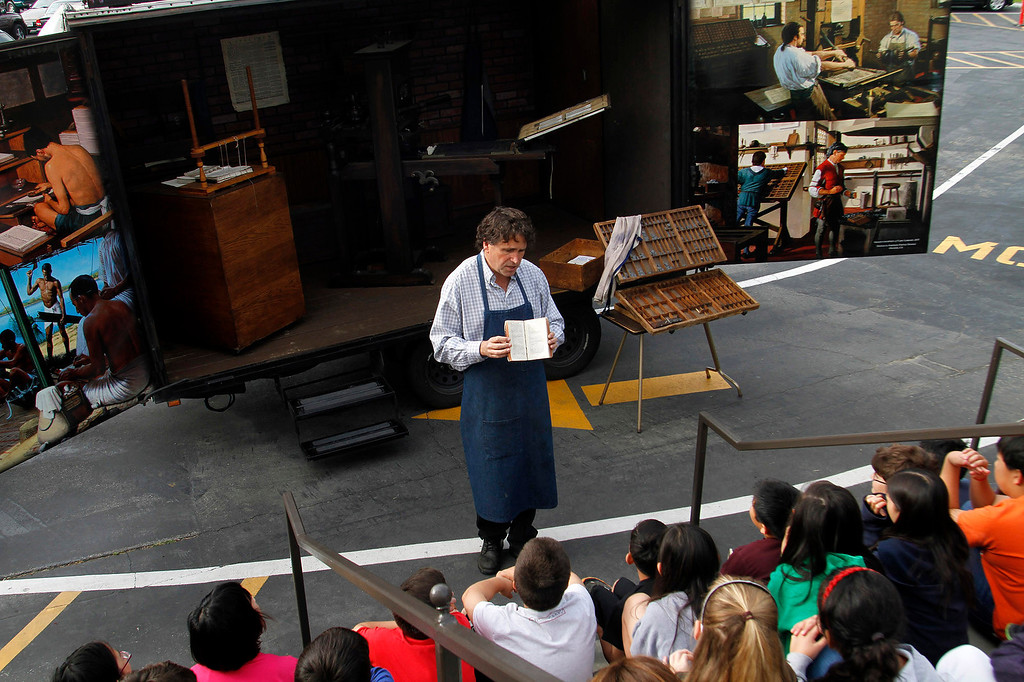". Mark Barbour, Executive Director and Curator of the International Printing Museum, gives a history leason on books and printing before Gutenberg to Benjamin Franklin\'s, using his ""Museum on Wheels\"" to the fifth grade class, at St. Marks Luthern School, in Hacienda Heights, Thursday, March 28, 2013. (Correspondent Photo by James Carbone/HIGH)"