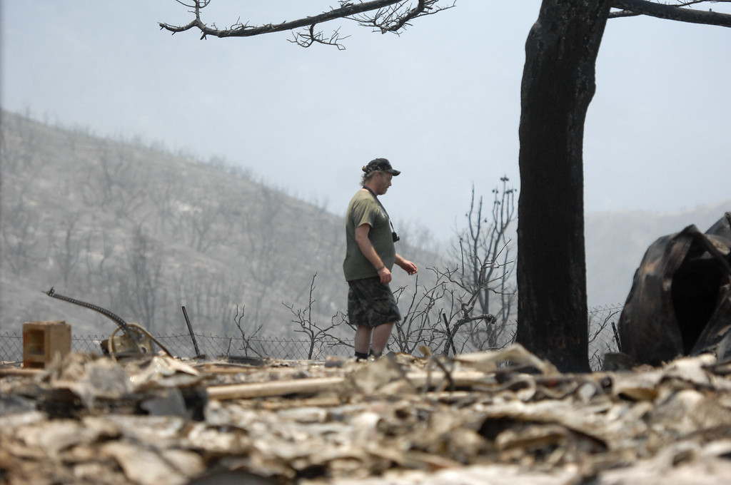 . Lake Hughes resident Jonathan Pehrson(cq) walks the grounds of a burnt house on Newview Drive in Lake Hughes from the Powerhouse Fire, Sunday, June 2, 2013. (Michael Owen Baker/Staff Photographer)