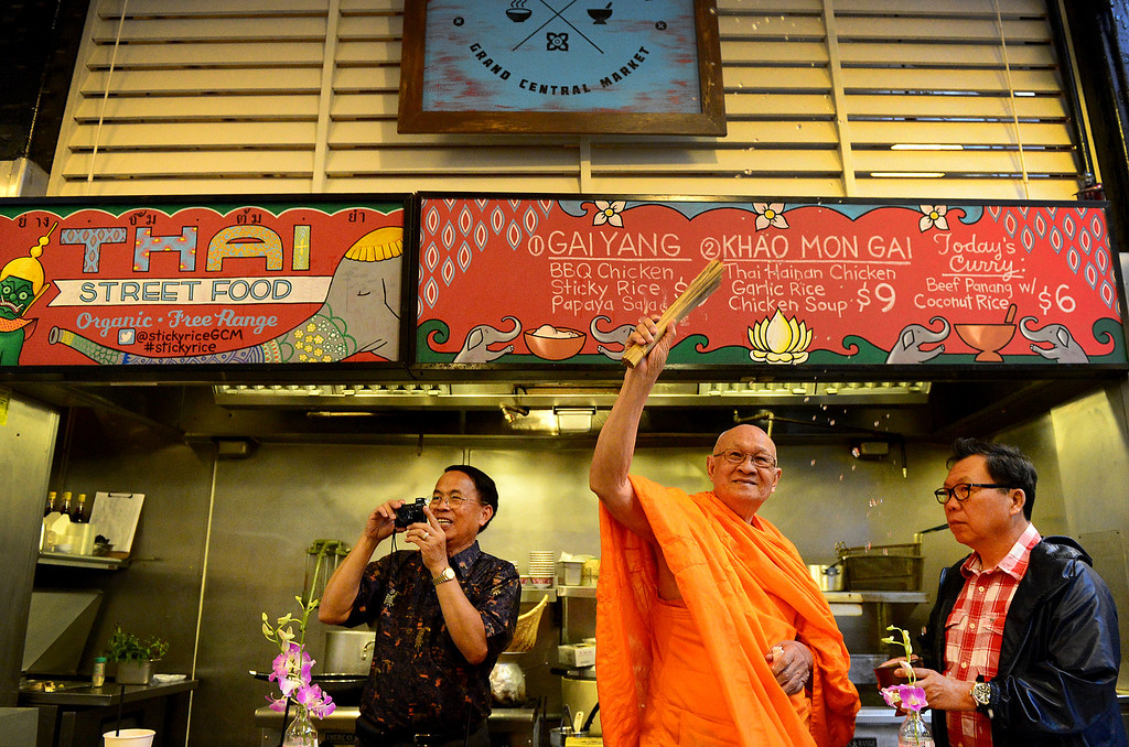 Description of . Wat Thai Temple's head monk Phra Rajthamvites blesses Pasadena resident David Tewasart's new business Sticky Rice at Grand Central Market in downtown Los Angeles Monday, April 30, 2013 as he is flanked by Chawapot