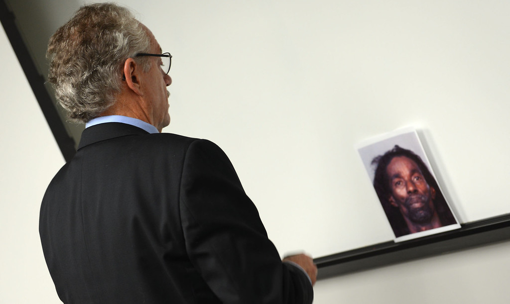 . Sherman Ballard looks at a booking photo of Jerome Anthony Rogers, 55, of San Bernardino during a San Bernardino press conference where police announced the arrest of Rogers in the killing of Mary Beth Blaskey. Ballard\'s mother-in-law, Wanda Paulin was murdered in her San Bernardino home in December 2010. Her killer remains at large. Rick Sforza/Staff photographer