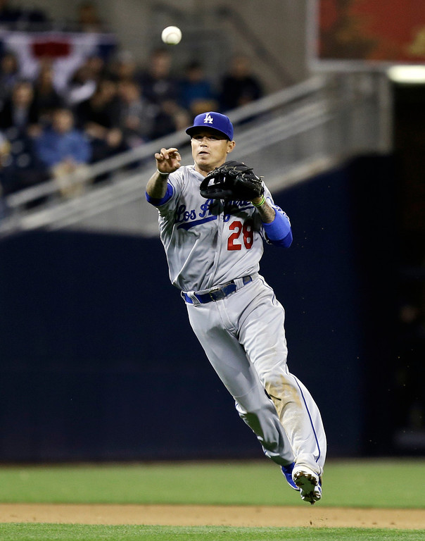 . Los Angeles Dodgers shortstop Justin Sellers makes the running off balance throw to get San Diego Padres\' Cameron Maybin out at first to end the fourth inning of a baseball game in San Diego, Thursday, April 11, 2013. (AP Photo/Lenny Ignelzi)