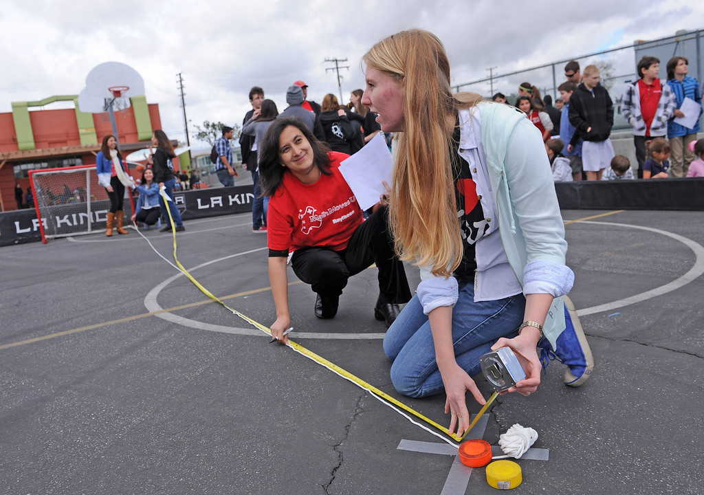 . Sarah Bixler, 11th grade, and Raytheon Space and Airborne systems engineer Martha Lee measure distance to the goal. Students teamed up with LA Kings players Justin Williams, #14, and Willie Mitchell #33 at DaVinci High School in Hawthorne to learn about geometry and how it plays into the game of hockey.   Photo by Brad Graverson 3-8-13