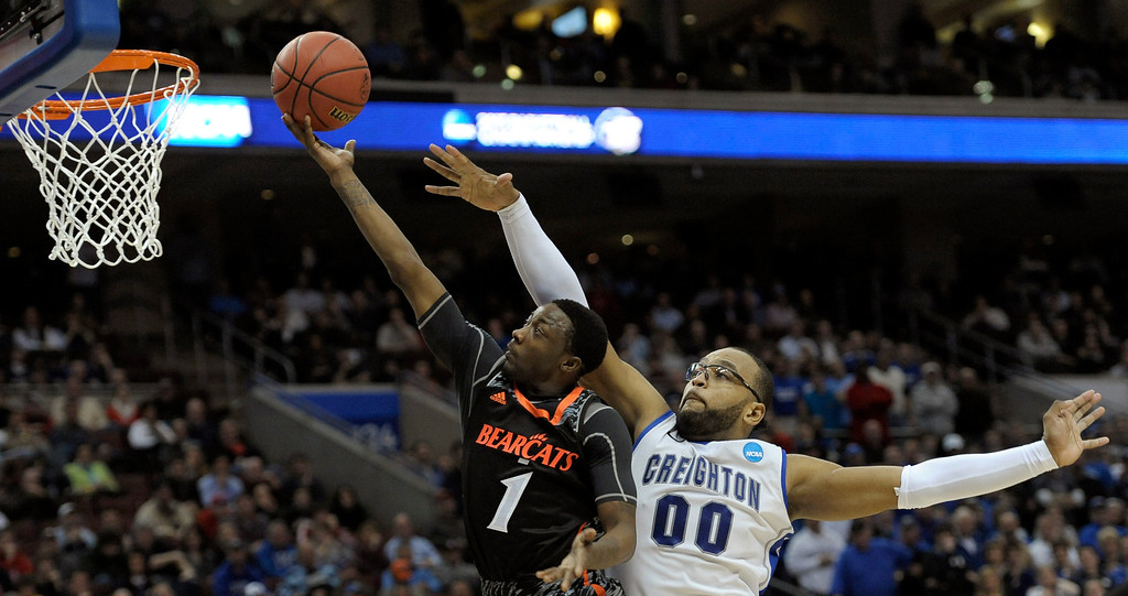 . Cincinnati\'s Cashmere Wright, left, goes up for a shot as Creighton\'s Gregory Echenique defends during the second half of a second-round game of the NCAA college basketball tournament, Friday, March 22, 2013, in Philadelphia. Creighton won 67-63. (AP Photo/Michael Perez)