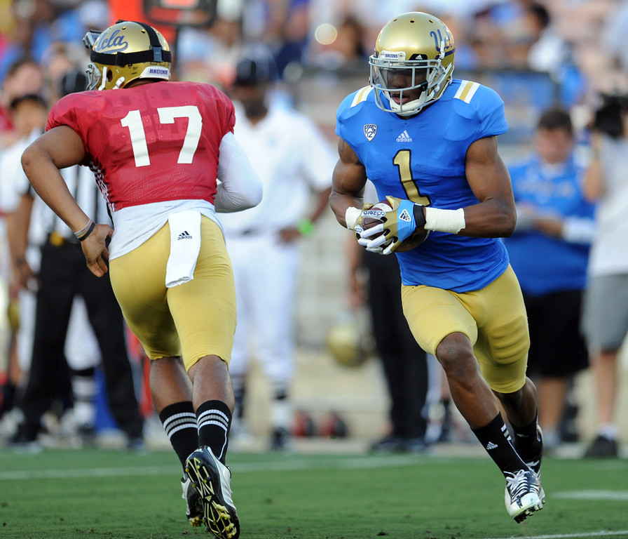 Description of . UCLA quarterback Brett Hundley (17) hands-off to wide receiver Shaquelle Evans (1) during the football spring showcase college football game in the Rose Bowl on Saturday, April 27, 2013 in Pasadena, Calif.    (Keith Birmingham Pasadena Star-News)
