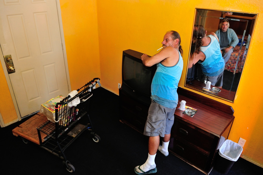 . El Capitan handyman, David, hooks up a television in the room of Tim Grobaty. Televisions are stored in a seperate storage room and delivered on request.Photo by Thomas Wasper for the Press Telegram