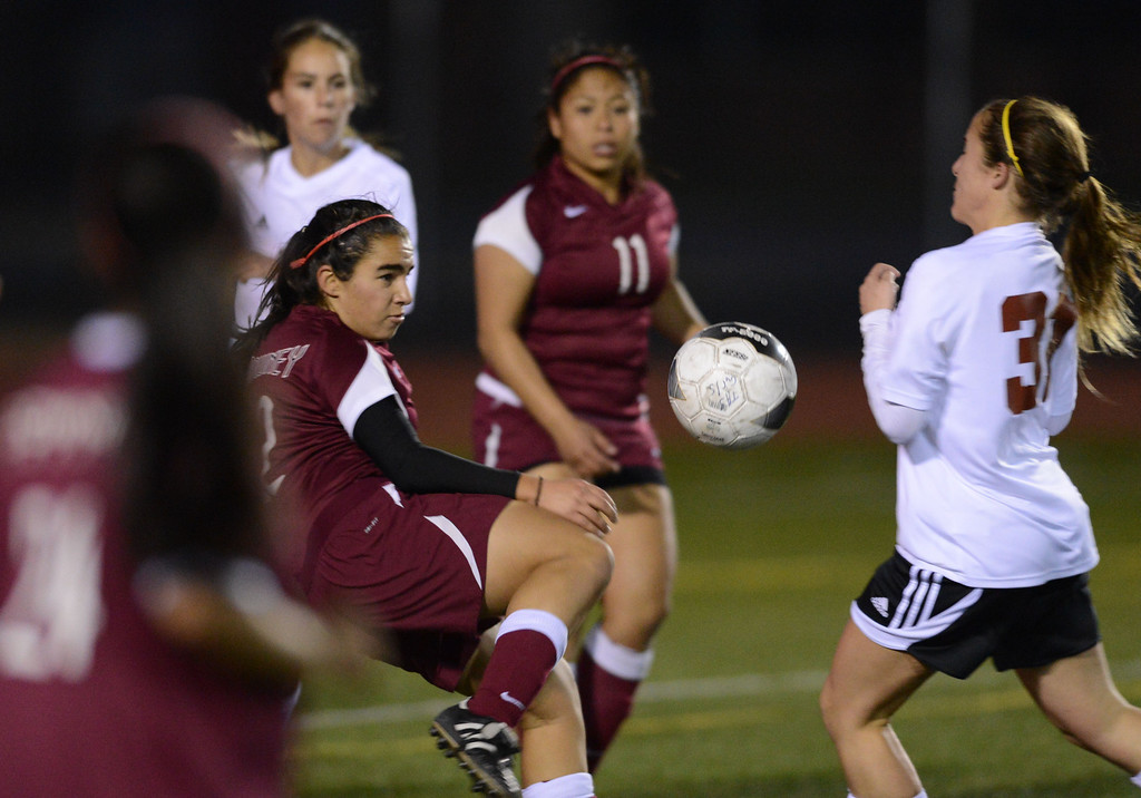 . Downey\'s Tara Kazimi (22) boots the ball past Torrance\'s Brianna Brown (31) in a CIF SS Division IV quarterfinal game Thursday at Zamperini Field. Downey won the game 3-1. 20130221 Photo by Steve McCrank / Staff Photographer
