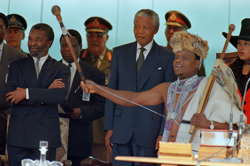 . A Praise singer, dressed in native costume and wielding a ceremonial cane, sings praises as Nelson Mandela stands behind him at the starts of the Presidential Inauguration ceremony in Pretoria Tuesday, May 10, 1994. At far is Mr. Mandela\'s daughter, princess Zenani Dlamini Mandela. Others unidentified. (AP Photo/David Brauchli)