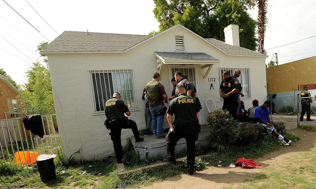 Description of . SMASH unit officers conduct a sweep at a home along the 1100 block Mayfield Drive in San Bernardino April 4, 2013.GABRIEL LUIS ACOSTA/STAFF PHOTOGRAPHER.