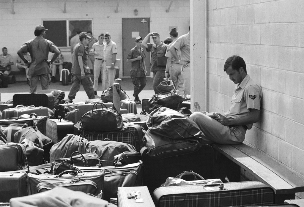 Description of . Surrounded by luggage of other departing GIs, U.S. Air Force airman reads paperback novel as he waits to begin processing at Camp Alpha on Saigon's Tan Son Nhut airbase in Saigon as troop withdrawals resume after 10 day-delay, March 27, 1973. More than 900 will leave with all U.S. troops out by Thursday. (AP photo/Charles Harrity)