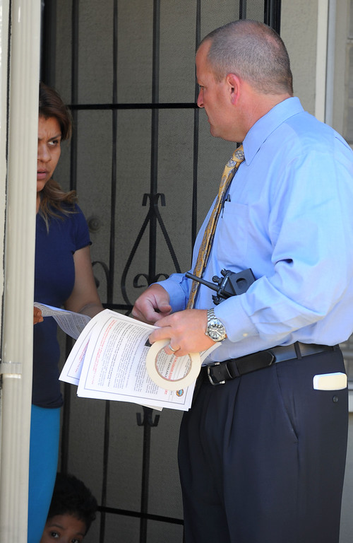 ". Long Beach police detective Don Collier hands out fliers to people in a neighborhood surrounding 7th Street and Orange Avenue in Long Beach, CA on Tuesday, May 13, 2014. The LBPD is looking for witnesses or anyone with knowledge of the March 24 shooting at the Cerritos Mini Market which left owner Felix Avela in critical condition after being shot during a robbery. The suspect is described as a black male in his late teens or early 20\'s with an average build and wearing a black hoodie sweatshirt with the word ""Cali\"" on the front. Anyone with info is asked to call LBPD at 562-570-7464 or 800-222-TIPS. (Photo by Scott Varley, Daily Breeze)"