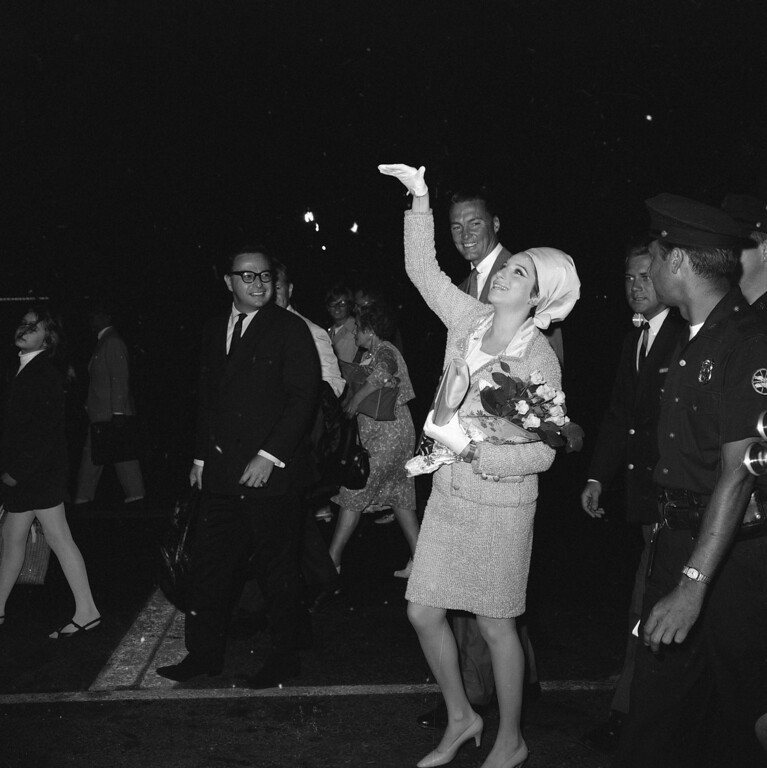 ". Barbra Streisand, star of ""Funny Girl,\"" arrives at Kennedy Airport in New York July 17, 1966 from London, where she starred in three-month run of the musical show.     New York Commissioner of Public Events Bud Palmer smiles behind Miss Streisand\'s upraised arm as she waves to fans.   Palmer gave her the flowers.  Miss Streisand, wife of Elliott Gould, expects a baby in December.    (AP Photo/Ray Howard)"
