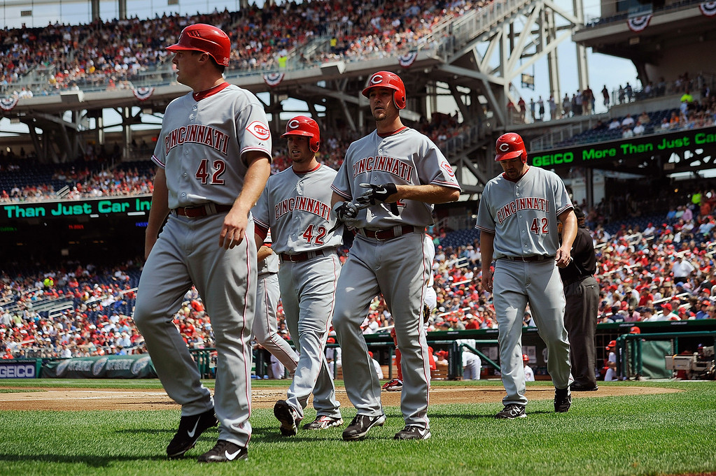 Description of . WASHINGTON, DC - APRIL 15:  Ryan Ludwick walks off the field with teammates Zack Cozart, Scott Rolen, and Jay Bruce after hitting a grand slam against the Washington Nationals at Nationals Park on April 15, 2012 in Washington, DC. In honor of Jackie Robinson Day, all players across Major League Baseball will wear number 42. (Photo by Patrick McDermott/Getty Images)