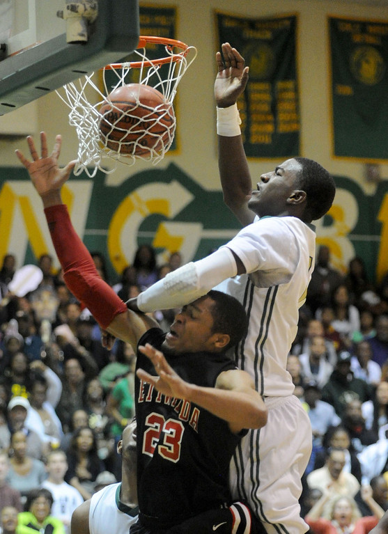 . 02-26-2012--(LANG Staff Photo by Sean Hiller)-Etiwanda beat Long Beach Poly 59-55 in Tuesday\'s CIF Southern Section Division 1AA semifinal boys basketball game at Long Beach Poly High School. Poly\'s Jordan Bell (2) goes over Eitwanda\'s Kenny Barnes (23) for a basket.