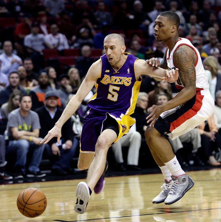 . Los Angeles Lakers guard Steve Blake, left, drives on Portland Trail Blazers guard Damian Lillard during the first quarter of an NBA basketball game in Portland, Ore., Wednesday, April 10, 2013. (AP Photo/Don Ryan)
