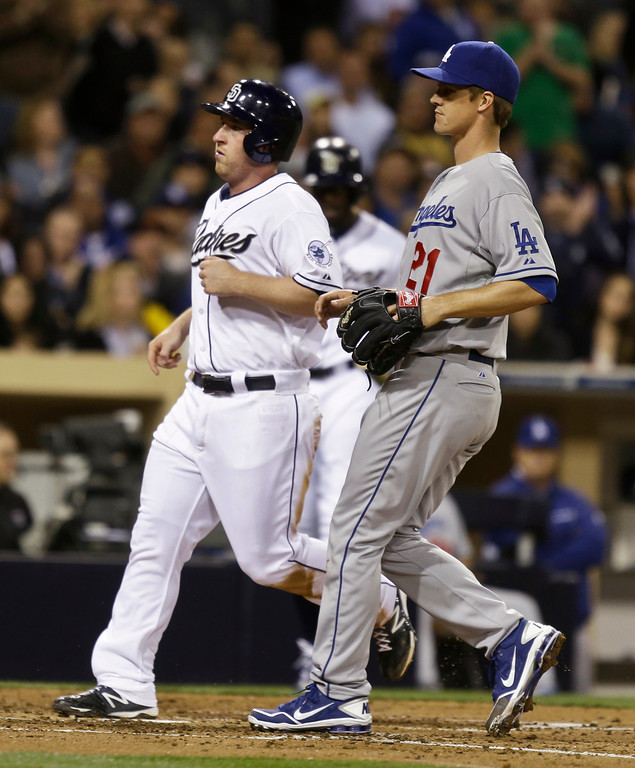 . San Diego Padres\' Jedd Gyorko, left, scores from third on a wild pitch as Los Angeles Dodgers pitcher Zack Greinke covers the plate during the fourth inning of a baseball game in San Diego, Thursday, April 11, 2013. (AP Photo/Lenny Ignelzi)