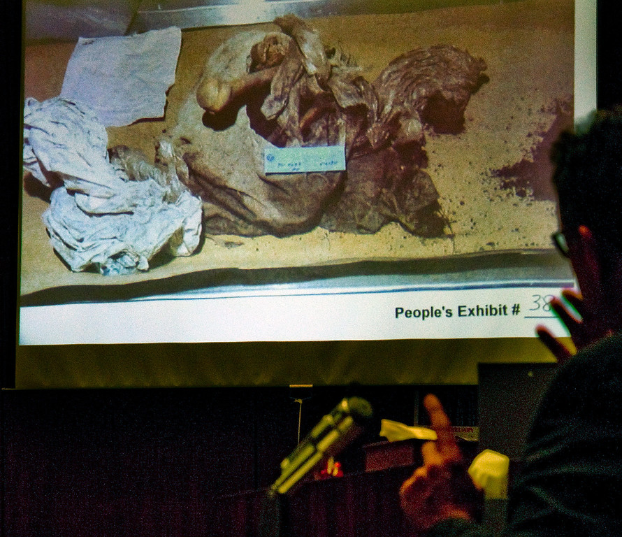 Description of . Manuel Munoz who worked at a coroner looking at projected photo taken of himself  when he was a coroner examining the body of John Sohus  and examined the evidence.(SGVN/Photo by Walt Mancini/LANG)