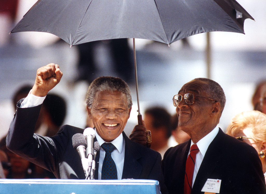 . June 1990: Nelson Mandela salutes the cheering crowd outside L.A. City Hall as an aide to Mayor Tom Bradley shields him from the sun.  Daily News file photo