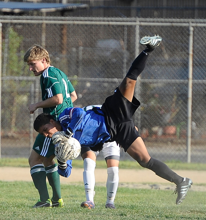 . March 4,2013. Canoga Park. Canoga Park GK  #21 Kevin Gonzalez block the ball as he lands on his teammate #20 Omar Solarzano, as Canoga took the win 2-0 over   Coronado during the first round of Southern California Div. II boys soccer regional playoffs   Photo by Gene Blevins/LA DailyNews