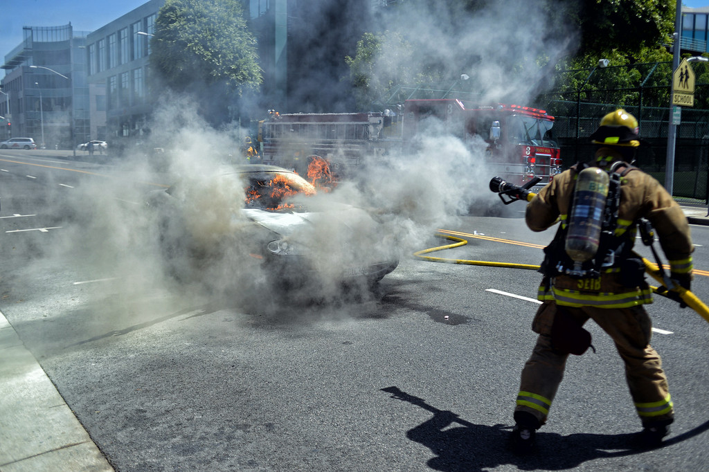 . Beverly Hills Fire Department firefighters put out a  car fire in front of 141 S Robertson Blvd, Beverly Hills, CA Tuesday, July 16, 2013. The female driver was able to exit the vehicle and was unhurt. (Hans Gutknecht/Los Angeles Daily News)