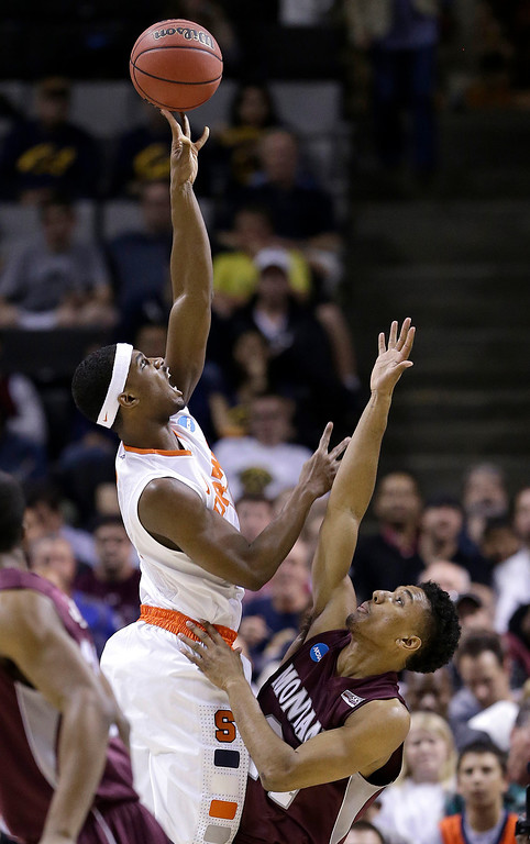 . Syracuse forward C.J. Fair, left, shoots over Montana forward Spencer Coleman during the first half of a second-round game in the NCAA college basketball tournament in San Jose, Calif., Thursday, March 21, 2013. (AP Photo/Jeff Chiu)