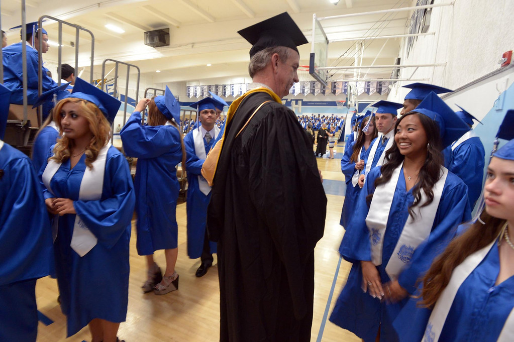 . Calculus teacher Robert Black talks to students before the start of ceremonies. The 2013 North High School commencement ceremonies take place on the school\'s football field in Torrance Wednesday afternoon.