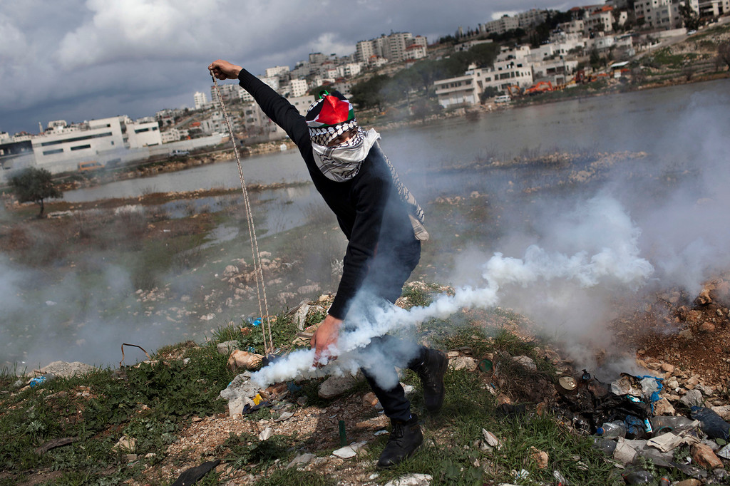 . A masked Palestinian throws back a gas canister previously shoot by Israeli forces, not pictured, during a protest to support Palestinian prisoners, outside Ofer, an Israeli military prison near the West Bank city of Ramallah, Tuesday, Feb. 19, 2013. Palestinian protesters clashed with Israeli soldiers at a rally Tuesday in support of four imprisoned Palestinians on hunger strike, as hundreds of inmates said they were refusing food for the day in solidarity with the fasting inmates. One of the four hunger-striking Palestinians is 35-year-old Samer Issawi whose health has severely deteriorated after he has refused food, on-and-off, for more than 200 days. (AP Photo/Bernat Armangue)
