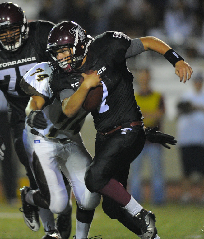 . West High takes on Torrance in a non league football game at Zamperini Stadium in Torrance, CA on Thursday, September 12, 2013. West won 46-7. Torrance QB Vincent Huey is chased down by Julian Gomez. (Photo by Scott Varley, Daily Breeze)