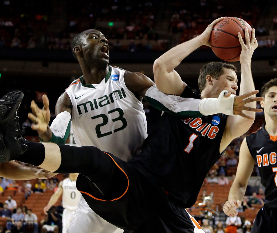 . Pacific\'s Trevin Harris (1) grabs a rebound in front of Miami\'s Tonye Jekiri (23) nduring the first half of a second-round game of the NCAA college basketball tournament Friday, March 22, 2013, in Austin, Texas.  (AP Photo/David J. Phillip)