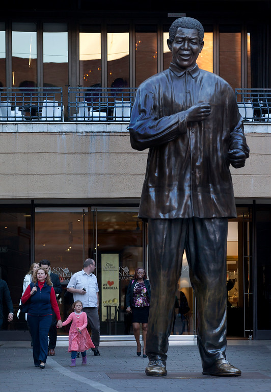 . Visitors walk past a statue of Nelson Mandela in Nelson Mandela Square at the Sandton City shopping centre in Johannesburg, South Africa Tuesday, June 11, 2013. Doctors are doing all they can to improve Nelson Mandela\'s health as the 94-year-old icon spent a fourth day in the hospital for a recurring lung infection, South Africa\'s president said Tuesday, as two of Mandela\'s daughters visited their father. (AP Photo/Ben Curtis)