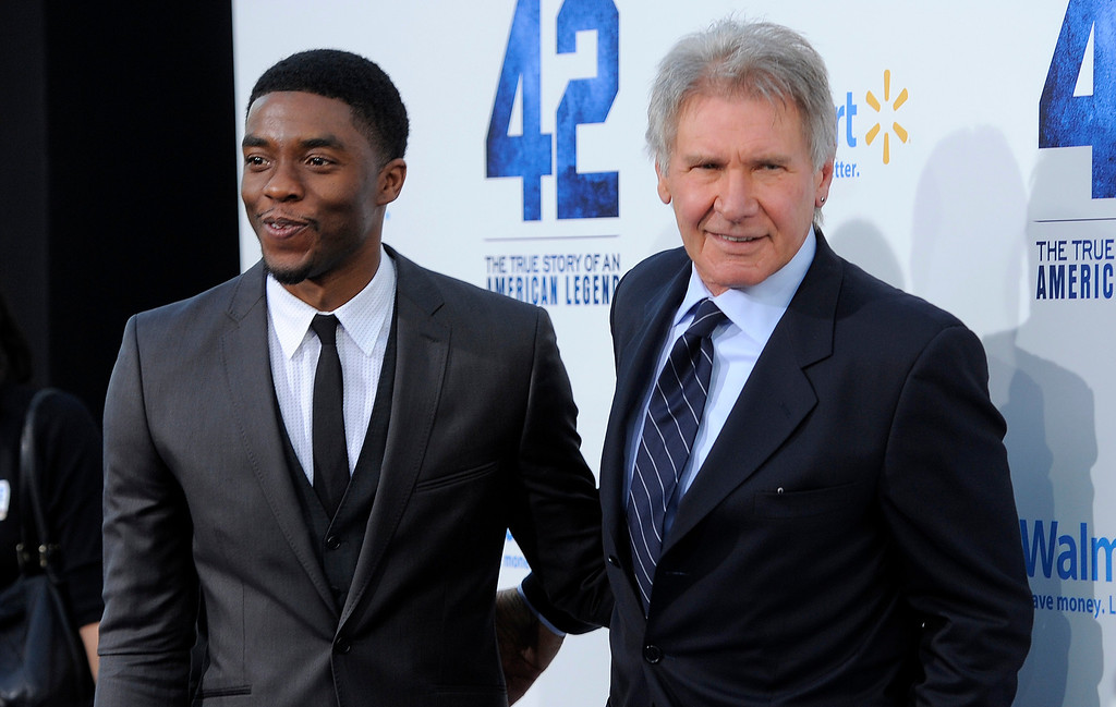 "Description of . Chadwick Boseman, left, who plays Jackie Robinson in ""42,\"" poses with fellow cast member Harrison Ford at the Los Angeles premiere of \""42\"" at the TCL Chinese Theater on Tuesday, April 9, 2013 in Los Angeles. (Photo by Chris Pizzello/Invision/AP)"