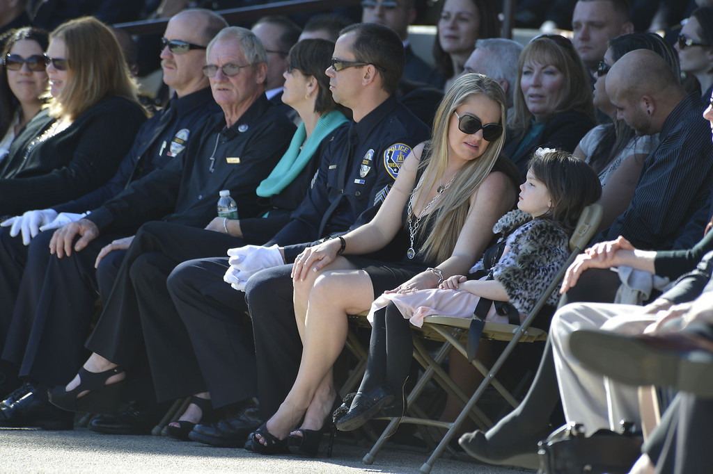 Description of . Family, friends and thousands of people, including law enforcement officials from across the state, arrived at the Grove Community Church this morning to attend the funeral service for Riverside Police Officer Michael Crain. Numerous California law enforcement joined all 400 members of the Riverside Police Department during the procession for Crain, 34, who was killed Feb. 7 when a suspect believed to be Christopher Dorner ambushed him and his partner while on duty.  (Jeff Gritchen/Staff Photographer)
