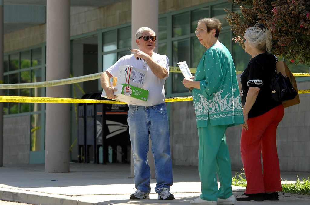 . People with packages to mail gather outside the West Hills post office on Sherman Way after a car crashed into the lobby Thursday morning, August 22, 2013. One person inside the post office was hurt and the post office closed for the day. (Michael Owen Baker/L.A. Daily News)