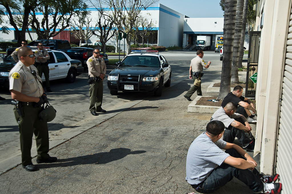 Description of . Los Angeles County Sheriff's deputies detain three employees as federal Food and Drug Administration officers serve a search warrant to auto parts dealer, L.A. Rush, in Norwalk on Friday, March 22, 2013. The business is suspected of illegally selling nitrous oxide for recreational drug use. (SGVN/Staff photo by Watchara Phomicinda)