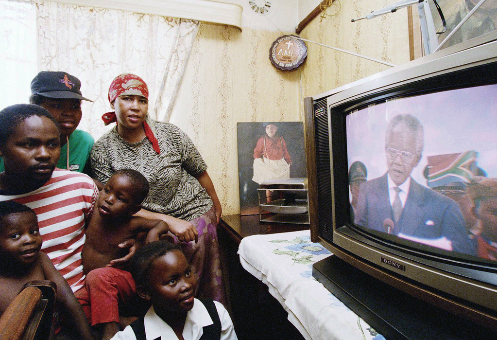 . Members of the Moledi family in Soweto, South Africa watch a live broadcast of the inauguration of President-elect Nelson Mandela in Pretoria, May 10, 1994. Mandela was sworn in as South Africa\'s first black president. (AP Photo/Joao Silva)