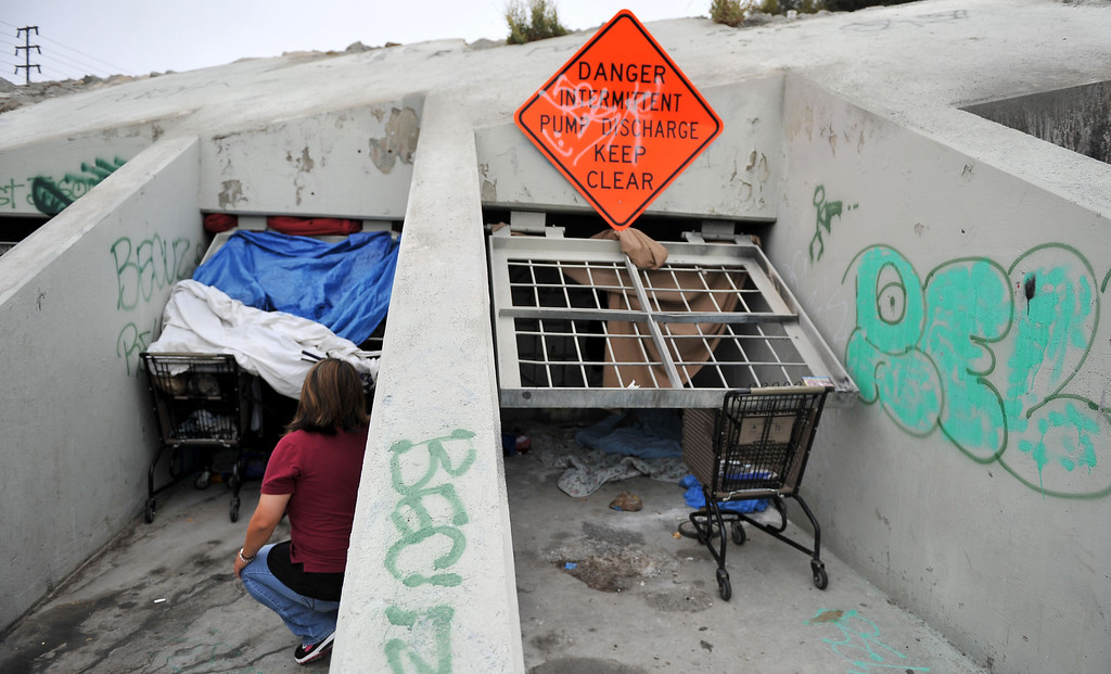 . 8/5/13 - Courtney Kanagi, director of outreach for (PATH) People Assisting The Homeless makes contact with a woman living in a storm drain Monday morning along the LA Riverbed and the 710 Freeway. The area is not as populated as years past but those facing chronic homelessness can still be found living under the bridges and in encampments. The county cleaned out the area in March 2013 and has stayed on top of the brush clearance and clean-up. Photo by Brittany Murray / Staff Photographer