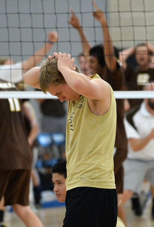 . Bishop Montgomery\'s Travis Pyrek (2) shows his disappointment as Parker celebrates on the other side of the net in a Southern California Regional Division III Final volleyball match Saturday at Santiago Canyon College in Orange. The match came down to the final points of the fifth game, with Bishop Montgomery losing the heart-breaker. Bishop Montgomery vs. Francis Parker (San Diego) 20130525 Photo by Steve McCrank / Staff Photographer