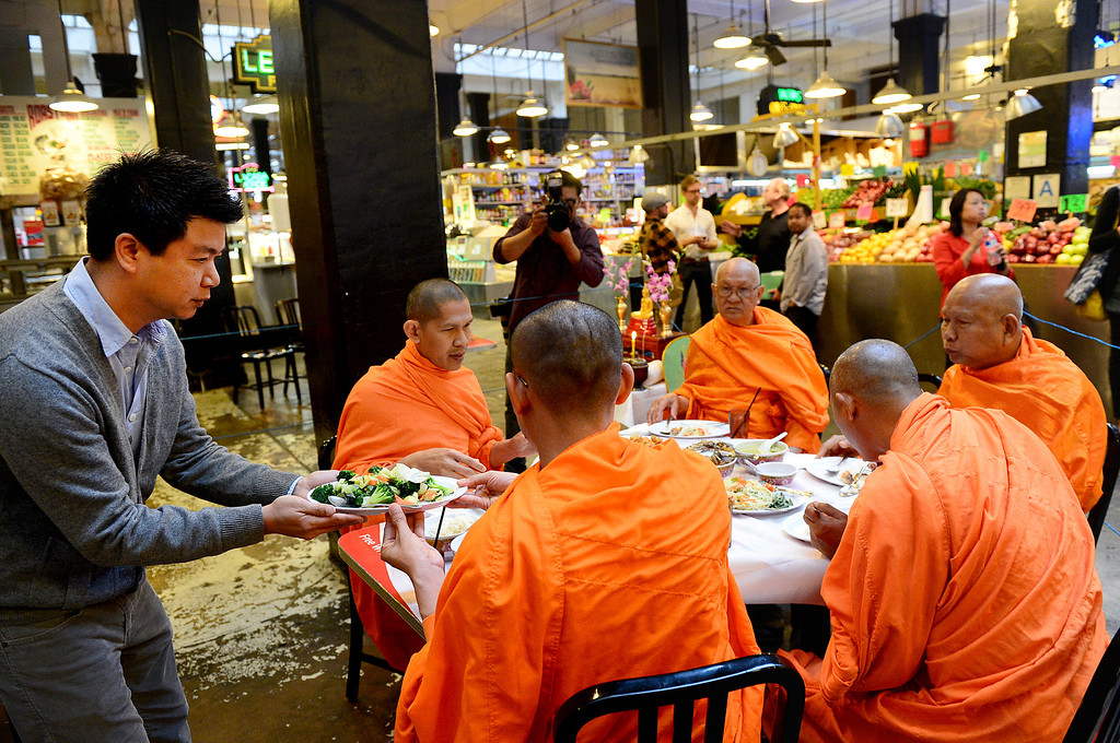 Description of . David Tewasart, of Pasadena, serves Wat Thai Temple monks, of North Hollywood, lunch after they blessed the opening of his restaurant Sticky Rice at Grand Central Market in downtown Los Angeles Monday, April 30, 2013. (SGVN/Staff Photo by Sarah Reingewirtz)