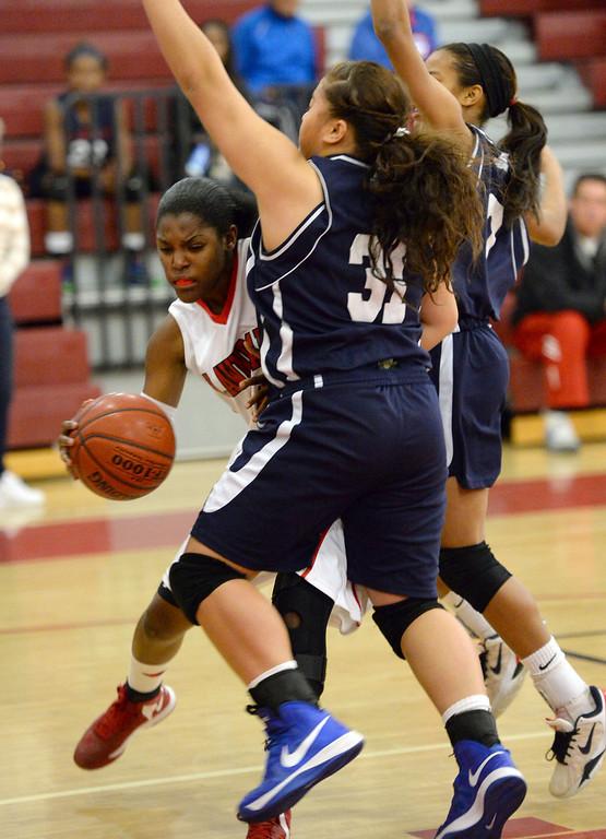 . Lawndale\'s Brittni Scott (14) drives the lane against Leuzinger\'s Uheina Tukutau (31) in a girls basketball game at Lawndale High Tuesday, December 10, 2013, in Lawndale, CA.  Photo by Steve McCrank/DailyBreeze