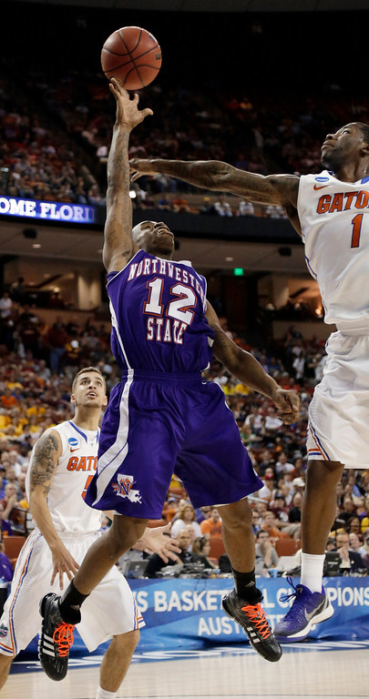 . Northwestern State\'s Jalan West (12) shoots as Florida\'s Kenny Boynton (1) defends during the second half of a second-round game of the NCAA men\'s college basketball tournament Friday, March 22, 2013, in Austin, Texas. Florida won 79-47. (AP Photo/David J. Phillip)