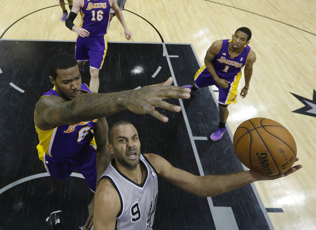 . San Antonio Spurs\' Tony Parker (9), of France, drives to the basket as he is defended by Los Angeles Lakers\' Earl Clark (6) during the second half of Game 2 of a first-round NBA basketball playoff series, Wednesday, April 24, 2013, in San Antonio, Texas. San Antonio won 102-91. (AP Photo/Eric Gay)
