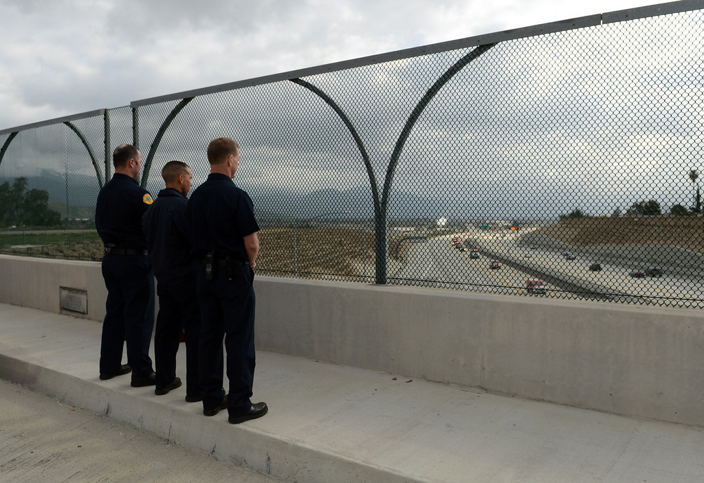 Description of . BN22-MACKAY-FUNERAL-08-JCM (Jennifer Cappuccio Maher/Staff Photographer) Members of the Rialto Fire Department watch the funeral procession for San Bernardino County Sheriff's Detective Jeremiah MacKay as it heads westbound on the 210 freeway Thursday, February 21, 2013, in Rialto.