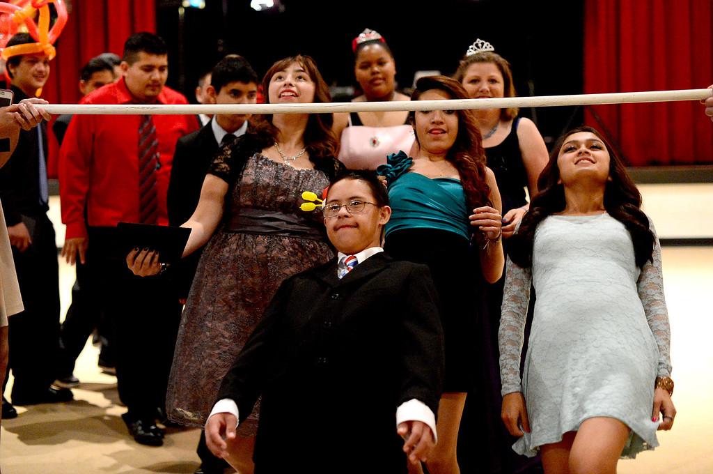 Description of . Students do the limbo dance during Glendora High School's Best Buddies Prom for high school students with special needs Friday night, April 19, 2013 at the Glendora campus. (SGVN/Staff Photo by Sarah Reingewirtz)